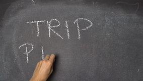 Hand writing `TRIP PLAN` on black chalkboard. Woman's hand writing TRIP PLAN with white chalk on blackboard stock video footage