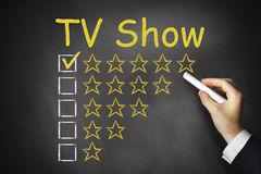 Hand writing tv show on black chalkboard Stock Images