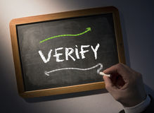 Hand writing Verify on chalkboard Royalty Free Stock Photo
