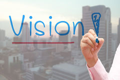 Hand writing Vision with blue marker  transparent wipe board and cityscape background. Royalty Free Stock Photo