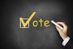 Hand writing vote checkbox on chalkboard Royalty Free Stock Photo