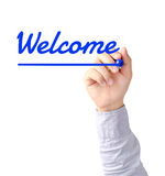 Hand writing Welcome with blue marker on transparent board. Right hand of young business man writing Welcome with blue marker on transparent board Stock Photography