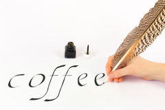 Hand writing the word COFFEE with a feather Royalty Free Stock Images