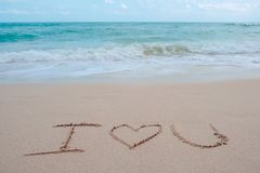 The hand writing word I love you on the beach by the sea with white waves and blue sky Stock Photography