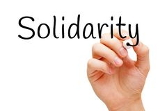 Solidarity Handwritten With Black Marker. Hand writing the word Solidarity with black marker on transparent wipe board isolated on white background stock photo