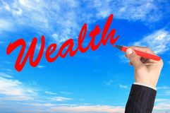 Hand writing word Wealth over blue sky Royalty Free Stock Image