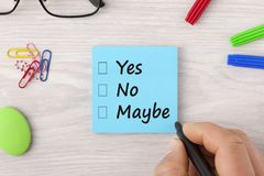 Yes No Maybe check boxes. Hand writing Yes No Maybe on note with marker pen and glasses on wooden desk. Business concept.Top view Stock Photo