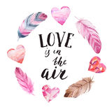 Hand written calligraphic love template card. `Love is in the air` hand brush lettering with watercolor heart and feathers for card, invitation and print. Ink Stock Images