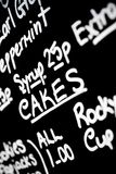 Hand written chalk menu board featured the word Cakes prominentl Royalty Free Stock Images