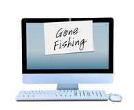 Hand written Gone Fishing sign taped to computer Stock Photo
