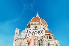 Hand written lettering card in girl`s hand with word Florence in front of Florence duomo. Travel Italy inspiration! Stock Images