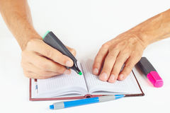 Hand written notes in green marker a notebook on white background Stock Photos