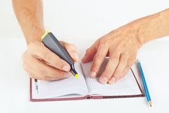 Hand written notes in yellow marker a notebook on white background Stock Photography