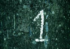 Hand written number one on grungy wall in cyan