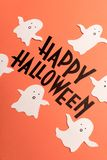Hand written phrase Happy Halloween with ghosts near it. Black typeface phrase for halloween logo with ghosts handwritten on orange background Stock Photos