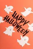 Hand written phrase Happy Halloween with ghosts near it Stock Photos