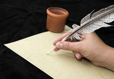 Hand writting with feather. Isolated on black  background Royalty Free Stock Photography