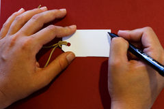Hand writting on a white tag Royalty Free Stock Images
