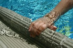 Hand of 5 years old boy holding edge of swimming pool. Hand of 5 years old boy holding ceramic edge of swimming pool. Ripples and small waves are flowing over stock images