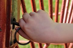 Hand of 6 years old boy unlocking old gate lock. On red house gate Stock Photography
