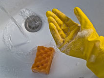 Hand in yellow glove. In soap, bathroom and water royalty free stock images