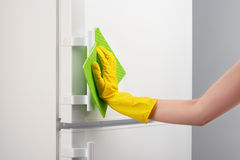 Hand in yellow glove cleaning white refrigerator with green rag Royalty Free Stock Images