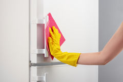 Hand in yellow glove cleaning white refrigerator with pink rag Royalty Free Stock Images