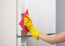 Hand in yellow glove cleaning white refrigerator with pink rag. Woman`s hand in yellow rubber protective glove cleaning white refrigerator with pink rag on gray Stock Image