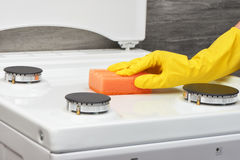 Hand in yellow glove cleaning white stove with orange sponge Stock Photos