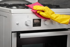 Hand in yellow glove cleaning white stove with pink rag Royalty Free Stock Photography