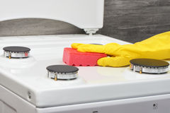 Hand in yellow glove cleaning white stove with pink sponge Royalty Free Stock Image