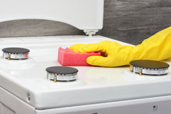 Hand in yellow glove cleaning white stove with pink sponge Stock Image
