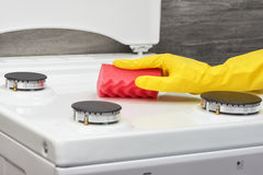Hand in yellow glove cleaning white stove with pink sponge Royalty Free Stock Images