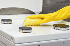 Hand in yellow glove cleaning white stove with sponge Stock Photos