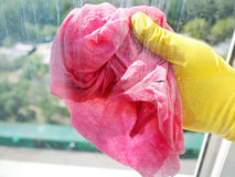 Hand in yellow glove cleaning window glass Royalty Free Stock Photos