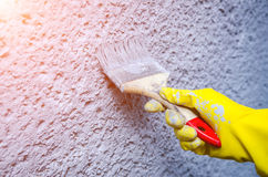 Hand in yellow glove holding paint brush and painting on wall. Hand in glove with a paint brush painting on wall. Decorator painting wall with blue paint Royalty Free Stock Photo