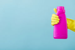 Hand in yellow glove holds a bottle of bleach on white background. cleaning Stock Images