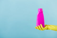 Hand in yellow glove holds a bottle of bleach on white background. cleaning Stock Photos