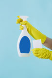 Hand in yellow glove holds spray bottle of liquid detergent and sponge on blue background. cleaning Stock Photography