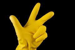 Hand in yellow glove making sign tree fingers Royalty Free Stock Images