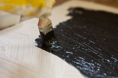 Hand in yellow glove paints a black surface with white stone. Copy Space Royalty Free Stock Photo