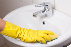 Hand in yellow glove with sponge cleaning sink Royalty Free Stock Image