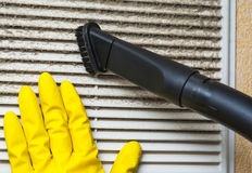 Hand in yellow glove and vacuum cleaner pipe Royalty Free Stock Photography