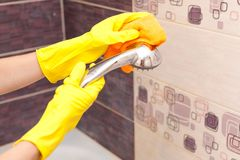 Hand in a yellow glove washes the shower royalty free stock image