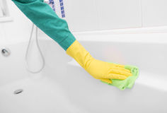Hand in yellow glove washes sink. Royalty Free Stock Photo