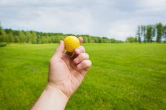 Hand with golf ball over a golf course. Hand with yellow golf ball over a golf course Royalty Free Stock Image