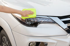 Hand with yellow microfiber cloth cleaning big white car. Stock Photo