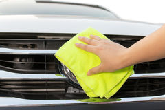 Hand with yellow microfiber cloth cleaning big white car. Stock Images