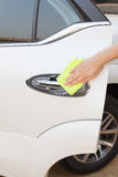 Hand with yellow microfiber cloth cleaning big white door car. Stock Image