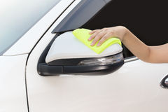 Hand with yellow microfiber cloth cleaning big white side mirror Stock Images